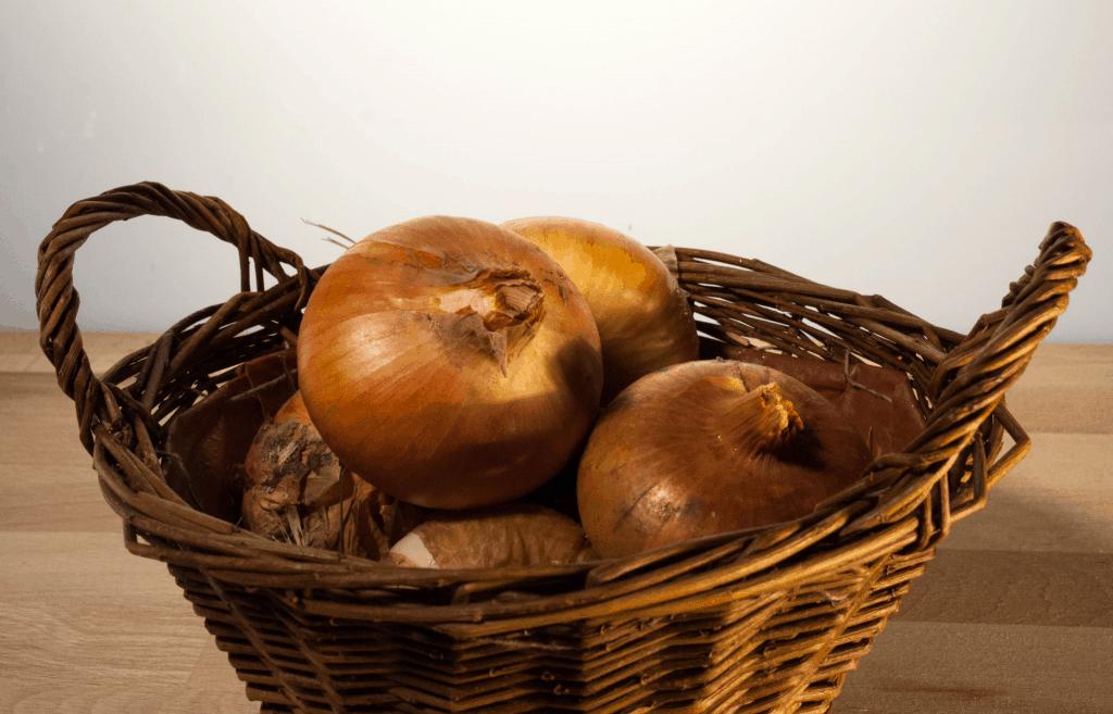 Einige abgetrocknete Zwiebeln in einem Korb.